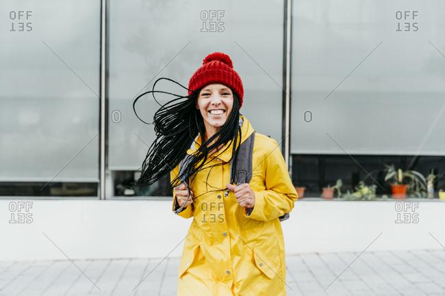 Woman wearing yellow raincoat standing on street