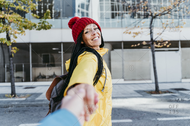 Woman holding friends hand while standing on street