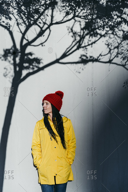 Woman wearing raincoat standing with hands in pockets under tree shadow against wall