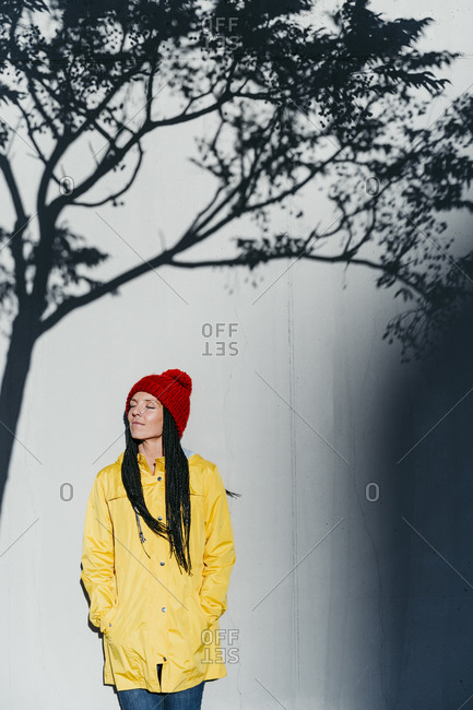 Thoughtful woman wearing raincoat standing with hands in pockets under tree shadow against wall