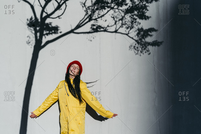 Contemplating woman wearing raincoat standing with  eyes closed under tree shadow against wall