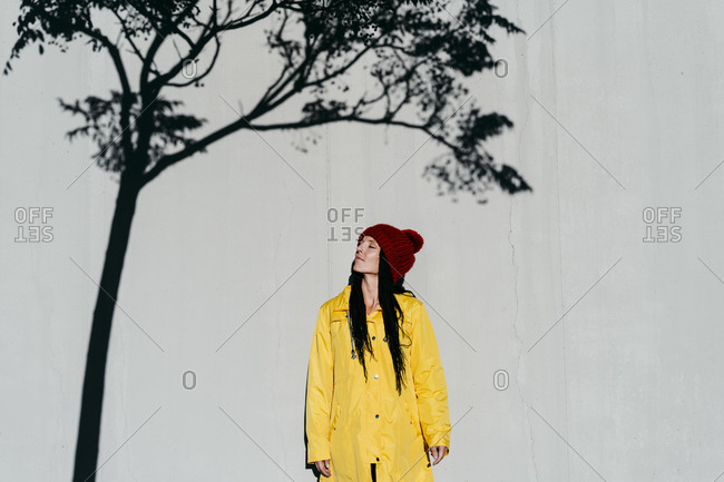 Woman wearing raincoat standing with  eyes closed under tree shadow against wall