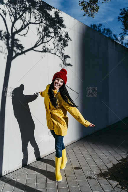 Smiling woman wearing raincoat standing on footpath by wall under tree shadow