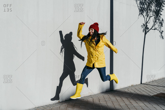 Cheerful woman wearing raincoat jumping on footpath by wall