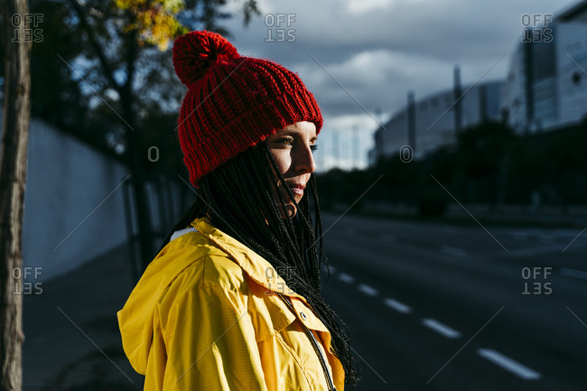 Thoughtful woman wearing knit hat standing on street during sunset