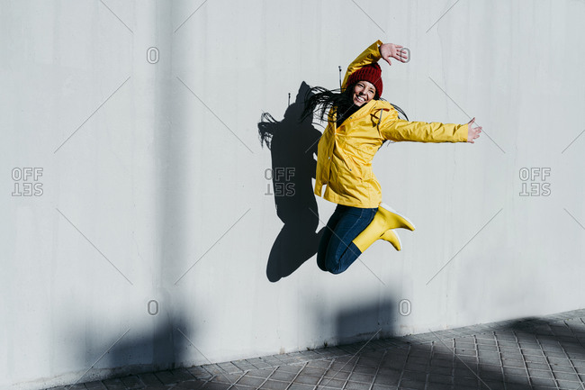 Cheerful woman with arms raised jumping by gray wall on footpath