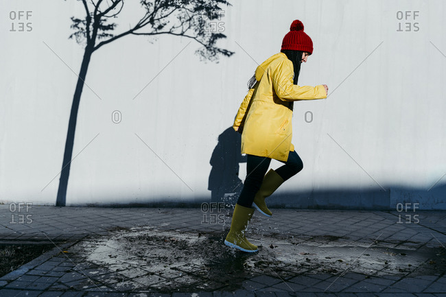 Woman wearing raincoat running on rain puddle by wall
