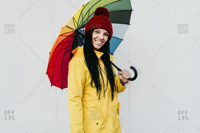 Smiling woman wearing raincoat holding colorful umbrella standing against wall