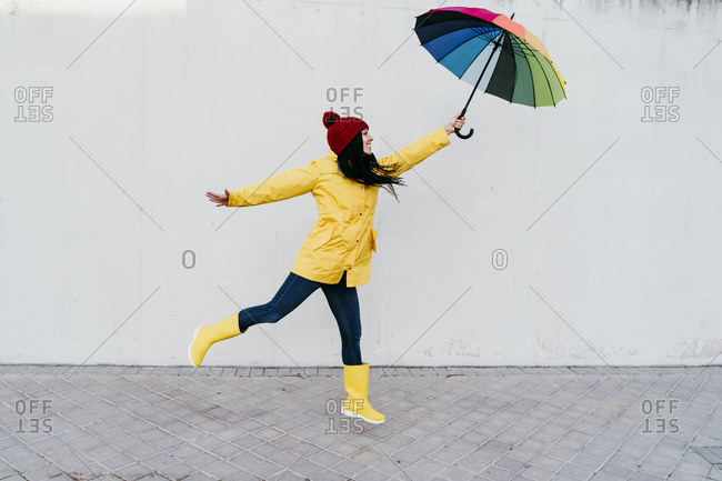 Woman with arms outstretched holding colorful umbrella while standing on footpath against wall