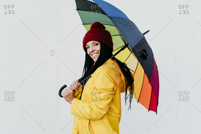 Smiling woman holding colorful umbrella while standing by wall
