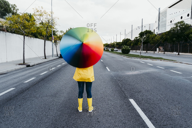 Woman holding colorful umbrella while standing on street