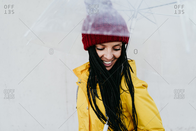 Smiling woman holding transparent umbrella while standing against gray wall