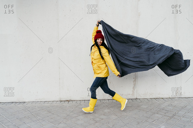 Woman wearing raincoat holding blanket while walking by wall on footpath