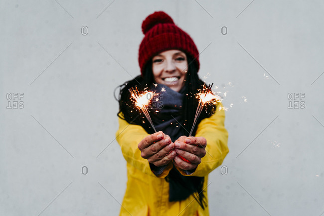 Smiling woman holding sparkler while standing against gray wall