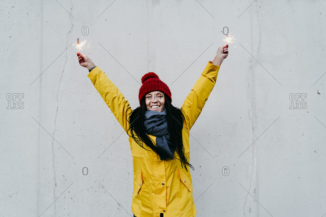 Smiling woman with hand raised holding sparkler while standing against wall