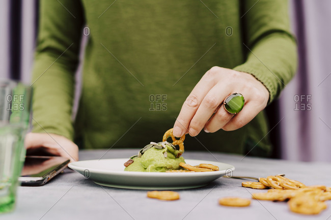 Close-up of woman eating pretzel with guacamole on table at home