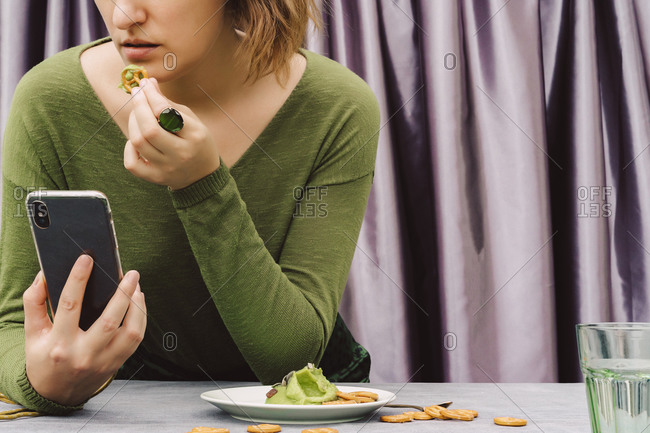Close-up of woman eating pretzel with guacamole using smart phone on table at home