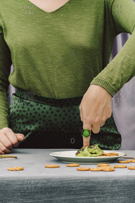 Close-up of woman with finger in guacamole on table at home
