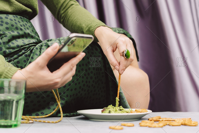 Close-up of woman using smart phone while eating guacamole and pretzel on table at home