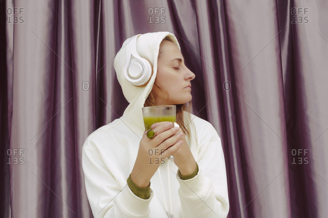 Woman with green juice listening music over headphones while standing against curtain at home