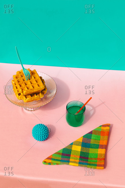 High angle view of waffle- juice- rubber ball and multi colored napkin kept on table