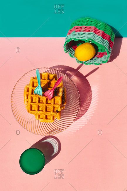 High angle view of waffle- lemon in basket- juice kept on table