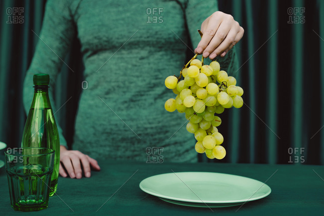 Midsection of woman holding grapes fruit while standing against green curtain