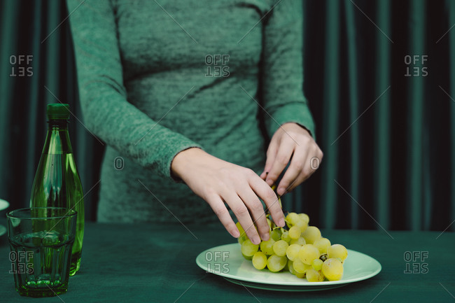 Midsection of woman with grapes- glass- bottle kept on table