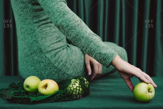 Midsection of woman with green apple touching while sitting on table against curtain
