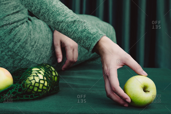 Midsection of woman green apple while sitting on table against curtain