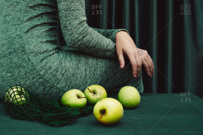 Midsection of female with green apple on table