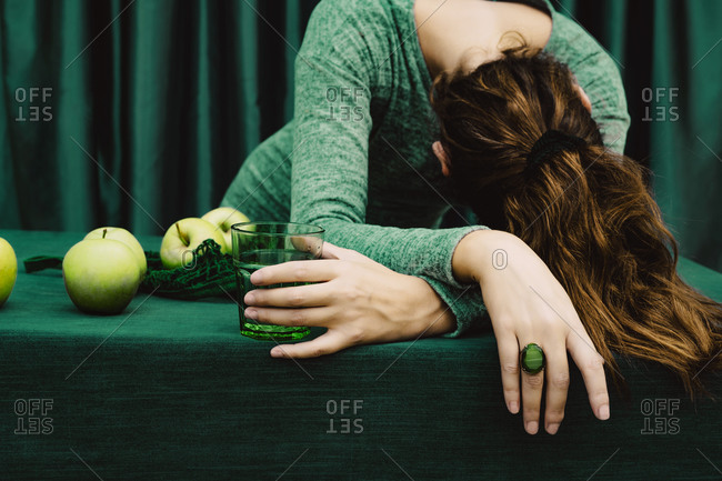 Mid adult woman with head down holding cocktail glass of drink against green curtain