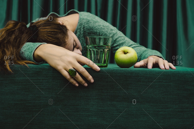 Woman lying on table with cocktail drink and green apple