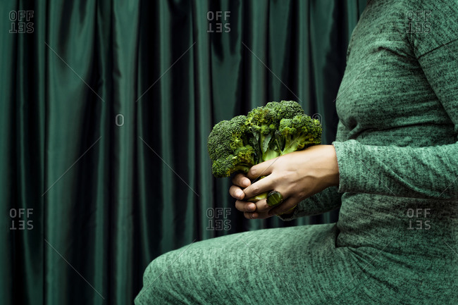 Midsection of woman holding broccoli while sitting by green curtain