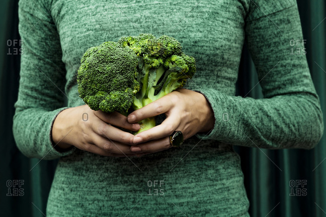 Midsection of woman standing with broccoli against curtain