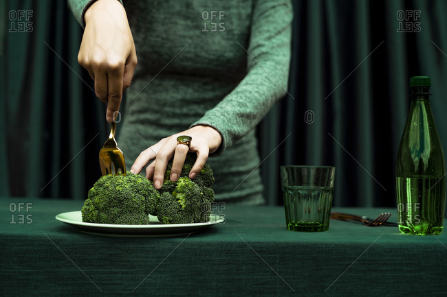 Midsection of woman cutting broccoli with fork kept in plate on table