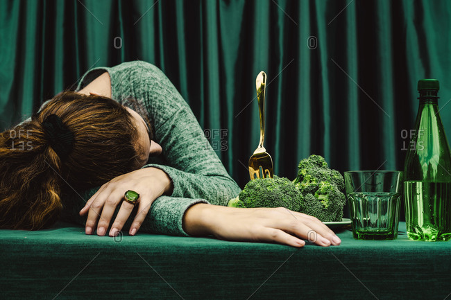 Mid adult woman lying with head down on table