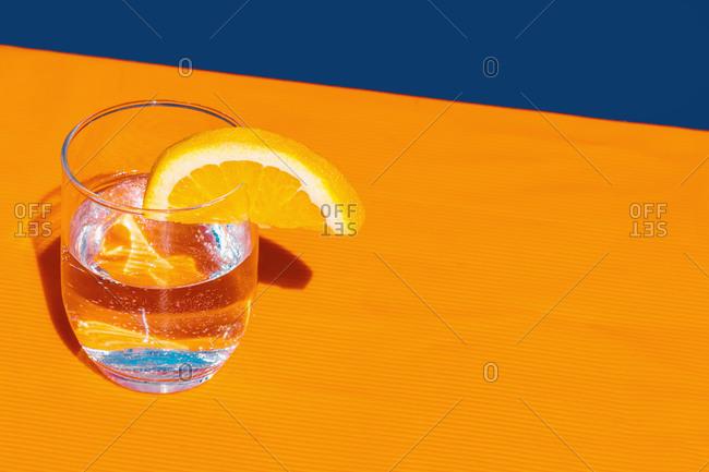 Studio shot of glass of soda with slice of lemon