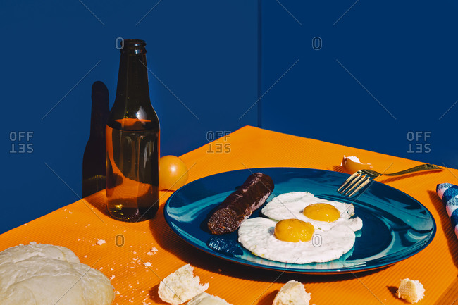 Bottle of beer and plate with fried eggs and chorizo