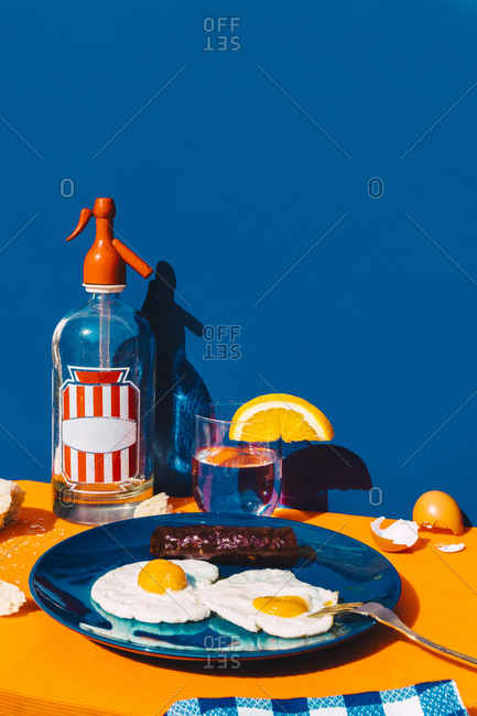 Studio shot of bottle of soda- glass of soda with slice of lemon and plate of fried eggs with chorizo