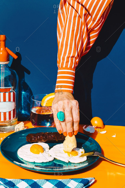 Arm of woman eating fried eggs with chorizo