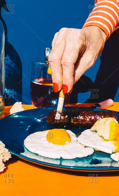 Hand of senior woman extinguishing cigarette in fried egg