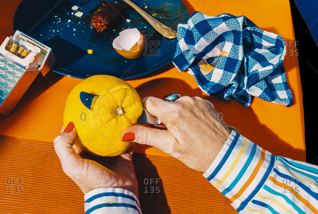 Hands of senior woman peeling orange with table knife