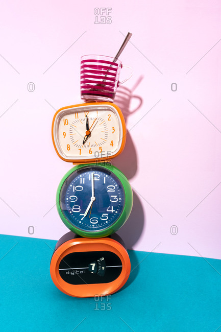 Coffee cup kept over clock stack against blue and pink background