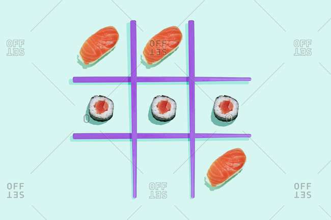 Tic-tac-toe game with salmon sushi maki and nigiri with purple chopsticks on mint green background