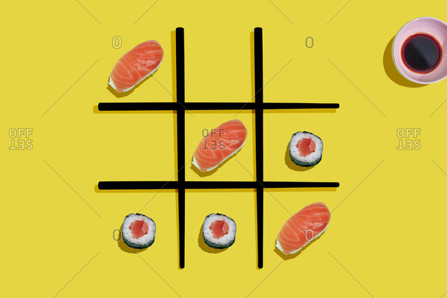 Tic-tac-toe game with salmon sushi maki and nigiri with black chopsticks on yellow background