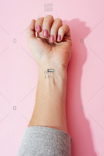 Cropped image of female hand with nail polish and USB port against pink wall