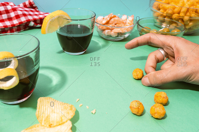 Hand of man playing with cheese puffs on table set with various snacks- appetizers and alcohol