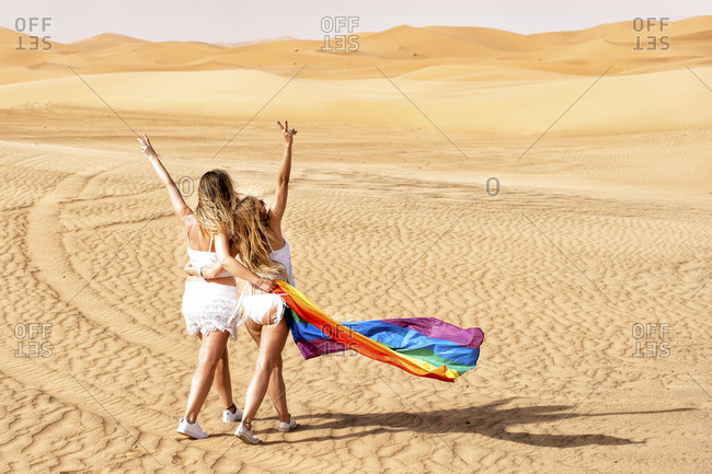 Mid adult women with gesturing peace sign while walking with flag at dessert
