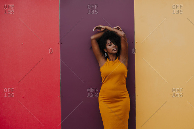 Thoughtful woman with arms raised standing against multi colored wall